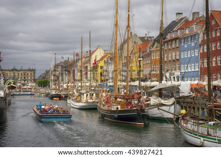 COPENHAGEN, DENMARK - JUNE 8:  Tour-boat, people and sailboats in Nyhavn Canal in Copenhagen, Denmark June 8, 2016 - stock photo