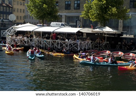 COPENHAGEN, DENMARK - JUNE 24: Unidentified active people in canoes and others relaxing in floating restaurants enjoy the life on Christianshavn - canal, on June 24, 2009 in Copenhagen, Denmark