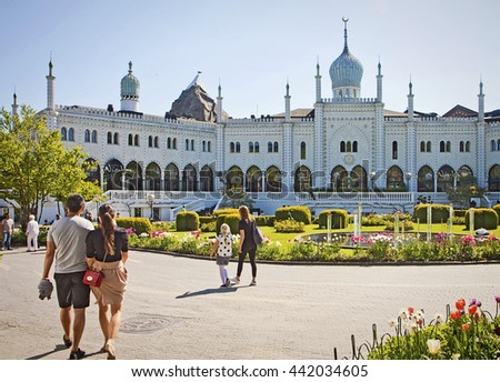 COPENHAGEN, DENMARK - MAY 8, 2016 Copenhagen, tourists in front of the Moorish Palace at Tivoli Gardens with beautiful fountain and bed flowers