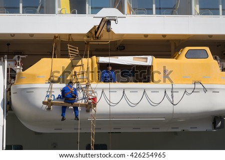 Copenhagen, Denmark - May 02, 2016: Men working on the lifeboats of the Cruise ship AIDAluna.