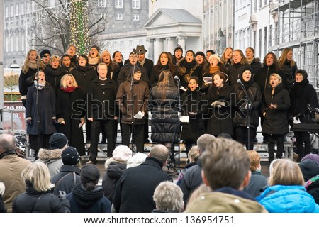 COPENHAGEN,DENMARK - November 17: a choir sings Christmas carols on a square in the city center, by-standers gathered in front of the stage, in 2012 - stock photo