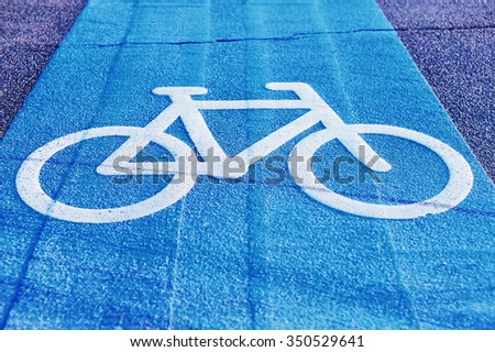 Copenhagen land of bicycles. Bicycle sign path on road. Bikes lane paint in blue.