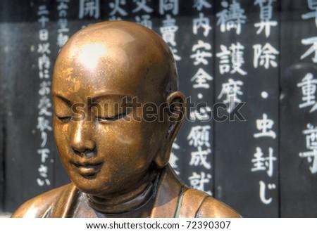 Copper Buddha near Tokyo's Senso-ji temple. - stock photo