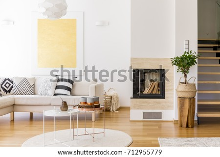 Copper coffee table on white carpet in living room with fireplace and gold painting on wall