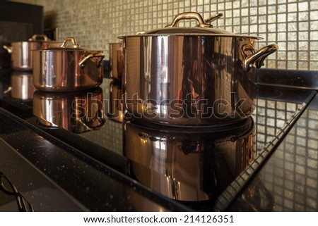 Copper cookware on the stove - stock photo