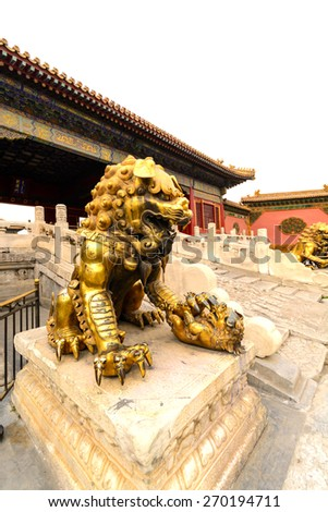 Copper lion in front of an ancient architecture in Forbidden city, Beijing China, white background - stock photo
