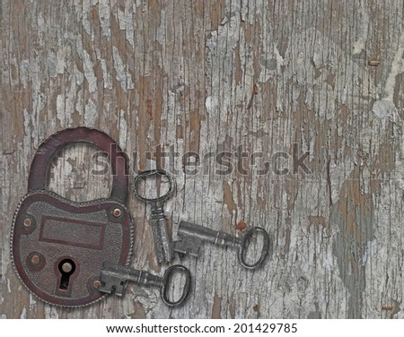 copper padlock and a keys on a weathered old wooden panel - stock photo