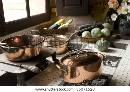 Copper pans on 17th century coal stove in preserved kitchen in an old chateau in Burgundy, France. Looks like a Dutch painted still life with fruit and natural light. - stock photo