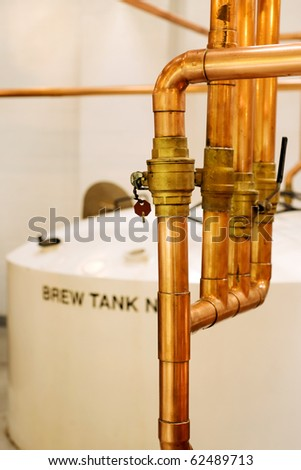 Copper pipes and tank in whisky distillery - stock photo