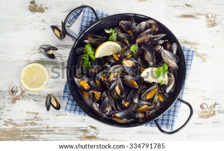 Copper pot of gourmet mussels served on a napkin garnished with lemon and parsley. Top view - stock photo