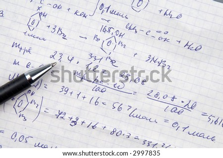 Copy-book sheet of paper with formulas and pen