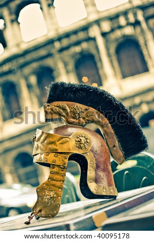 Copy of ancient helmet of Roman legionnaire against old Colosseum.Italy, Rome - stock photo