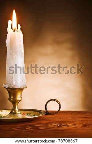 copy space ablaze candle in old candlestick - stock photo
