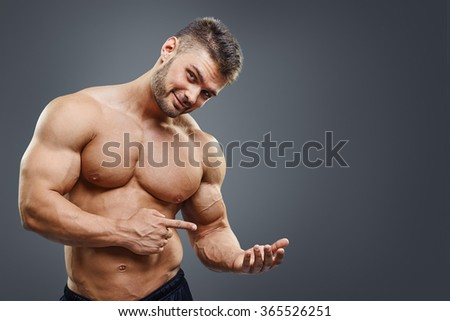 Copy space at his hand. Sexy shirtless muscular man holding copy space and looking at camera while standing against grey background. Place for product. - stock photo