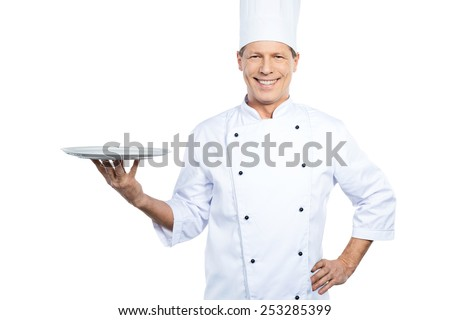 Copy space at his plate. Confident mature chef in white uniform holding empty plate and smiling while standing against white background - stock photo