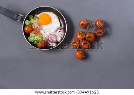 Copy space breakfast table with frying pan of fried eggs served with vegetables - stock photo