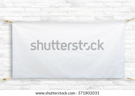 Copy space for text on disastrously white vinyl banner on white brick background .Clipping path horizontal - stock photo