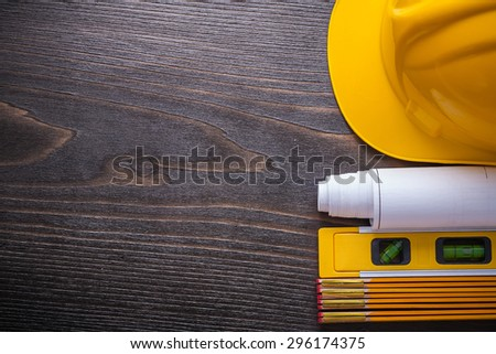 Copy space image of blueprints construction level building helmet and wooden meter on vintage wood board maintenance concept. - stock photo