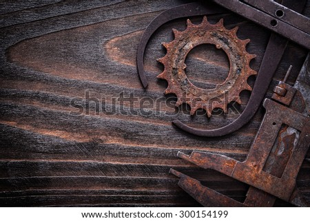 Copy space image of rusted measuring calipers with gear wheel on vintage dark wooden surface construction concept. - stock photo