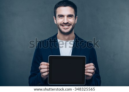 Copy space in his digital tablet. Cheerful young man showing his digital tablet and smiling while standing against grey background - stock photo