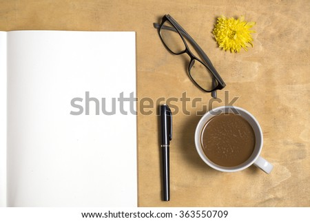 Copy space of notebook and coffee with glasses on old texture wooden table - stock photo