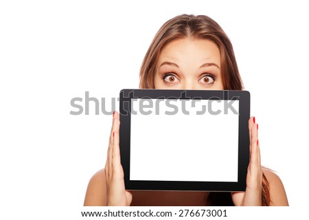 Copy space on her digital screen. Surprised young woman looking out of the tablet computer while standing isolated on white - stock photo