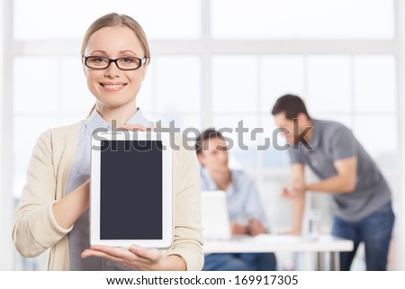 Copy space on her digital tablet. Confident young businesswoman in casual wear holding digital tablet and smiling while her colleagues talking on the background - stock photo