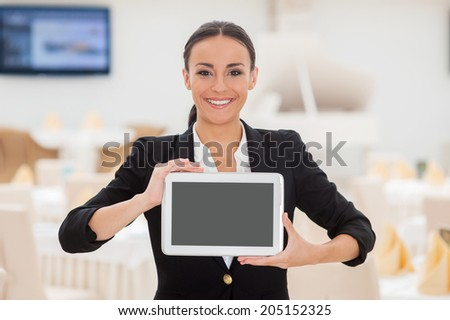 Copy space on her tablet. Beautiful young woman in formalwear showing her digital tablet and smiling while standing in restaurant - stock photo