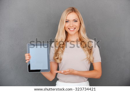 Copy space on her tablet. Cheerful young woman holding digital tablet and pointing at it while standing against grey background - stock photo
