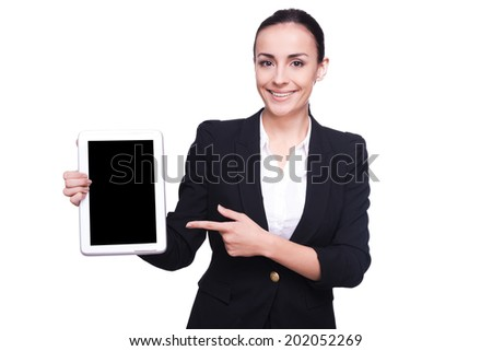 Copy space on her tablet. Confident young woman in formalwear pointing her digital tablet and smiling while standing isolated on white - stock photo