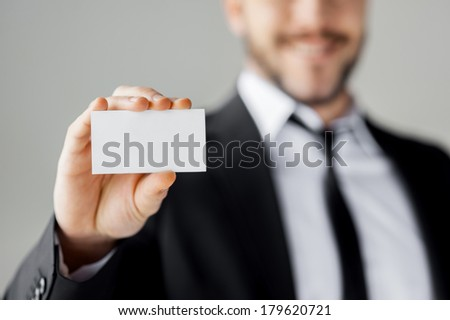 Copy space on his business card. Cheerful young man in formalwear showing his business card and smiling while standing against grey background - stock photo