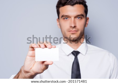 Copy space on his business card. Confident young man in shirt and tie showing his business card while standing against grey background - stock photo