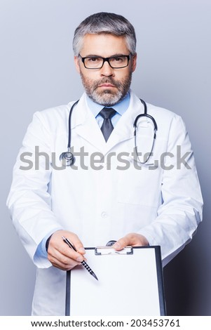 Copy space on his clipboard. Confident mature doctor looking at camera and pointing copy space on his clipboard  while standing isolated on white - stock photo