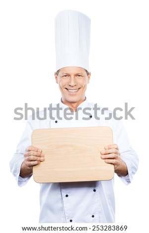 Copy space on his cutting board. Confident mature chef in white uniform holding wooden cutting board and smiling while standing against white background - stock photo