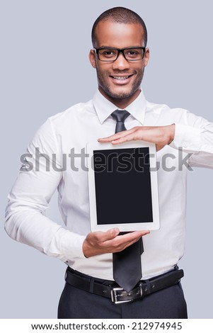 Copy space on his digital tablet. Confident young African man in shirt and tie showing his digital tablet and smiling while standing against grey background  - stock photo
