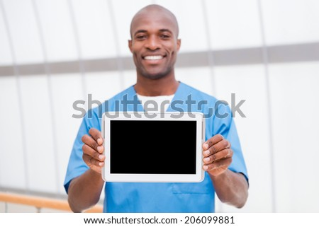 Copy space on his tablet. Cheerful young African doctor in blue uniform showing his digital tablet and smiling - stock photo