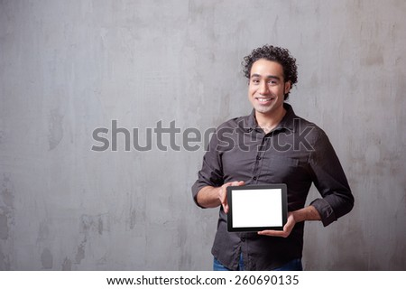 Copy space on his tablet. Cheerful young man holding a digital tablet and smiling while standing against grey background - stock photo