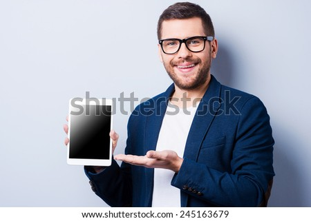 Copy space on his tablet. Cheerful young man showing a digital tablet and smiling while standing against grey background - stock photo
