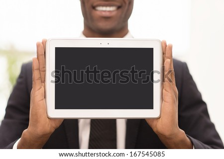 Copy space on his tablet. Cropped image of cheerful young African man in formalwear showing a screen of digital tablet and smiling at camera - stock photo