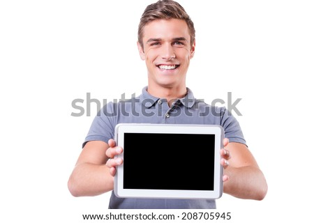 Copy space on his tablet. Happy young man showing his digital tablet and smile while standing isolated on white background - stock photo