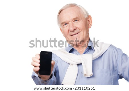 Copy space on my telephone. Portrait of happy senior man showing his mobile phone while standing against white background  - stock photo