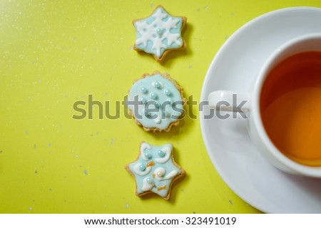 Copy space picture of handmade ginger cookies and cup of tea on green background, closeup - stock photo