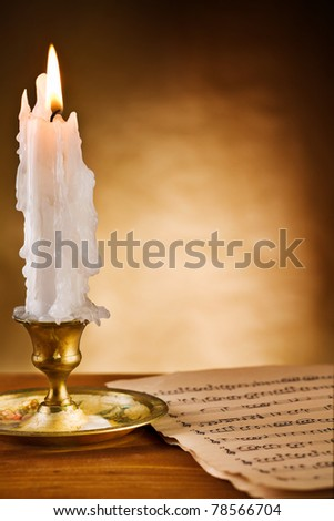 copy space view on the ablaze candle and old notes - stock photo