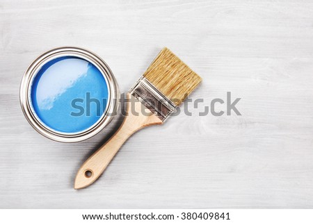 Copy space with paintbrush and can with blue paint lying on white wooden clean table. Top view. Copyspace. - stock photo