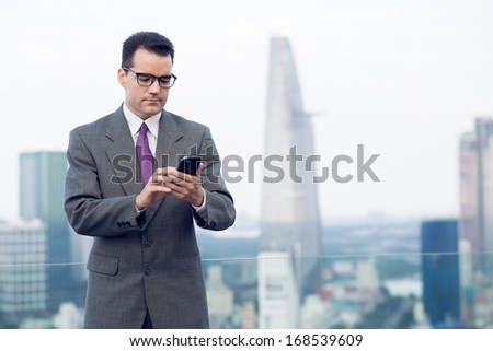 Copy-spaced image of a businessman making a serious call by smartphone standing on the roof  - stock photo
