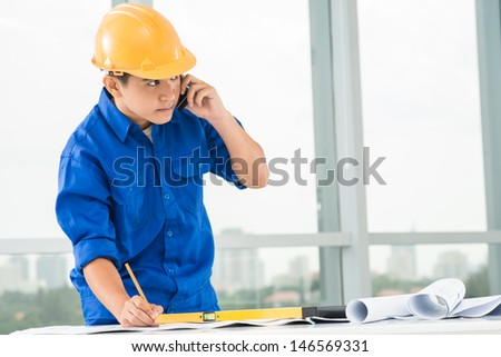 Copy-spaced image of a constructor worker talking by phone while sketching - stock photo