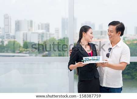 Copy-spaced image of a family couple where a husband embracing his wife while holding a paper miniature of their future house - stock photo