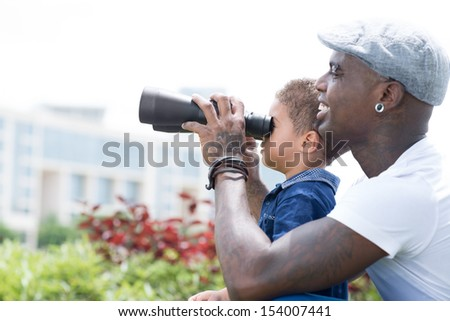 Copy-spaced image of a father and a son with binoculars outside - stock photo