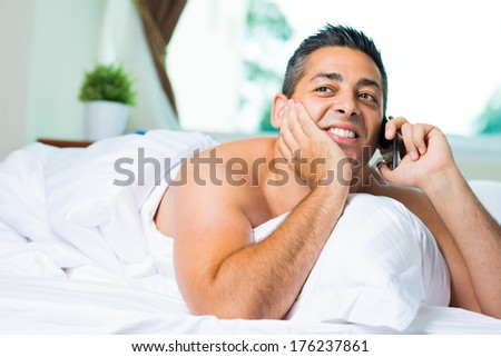 Copy-spaced image of a handsome man resting in bed and talking by phone on the foreground  - stock photo