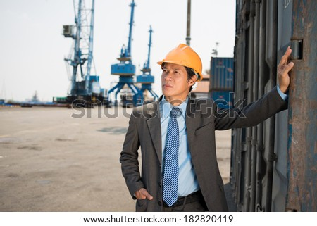 Copy-spaced image of a port engineer looking at objects on the foreground  - stock photo